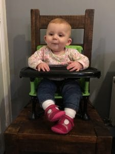 Ava sitting comfortably using the pop 'n' sit chair on an adults chair