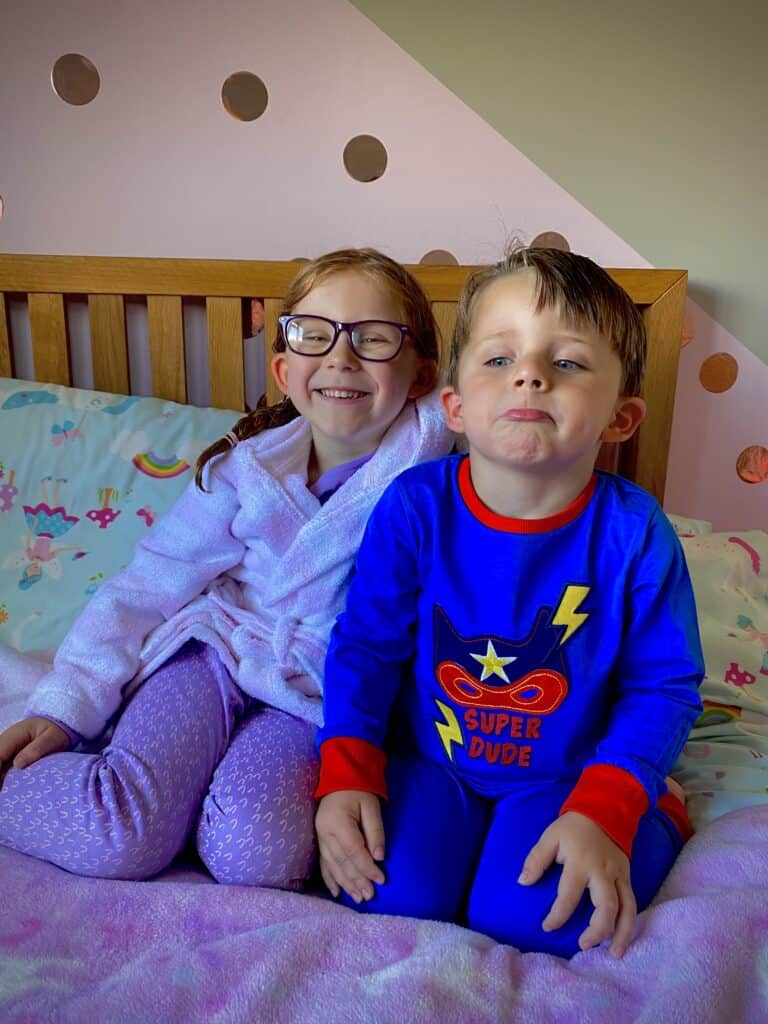 sibling sitting on a bed smiling